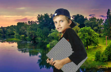 The boy with a folder against an evening landscape.