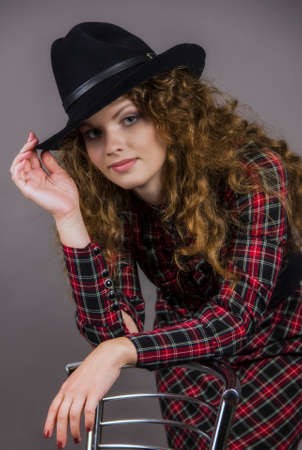 corrects: The girl in a checkered dress and a black hat. Stock Photo