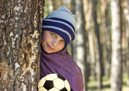 tenager: the boy with football in the spring wood.