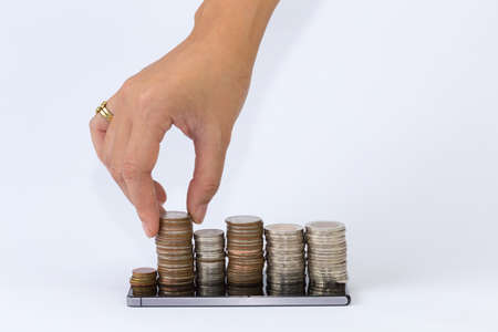 silver coins: hand putting silver coins to piles of coins arranged as a graph on the smart phone.