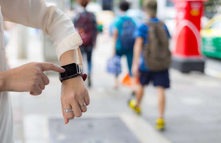 looking at watch: A femalewoman hand holdtouch a smart watch on her left hand. Stock Photo
