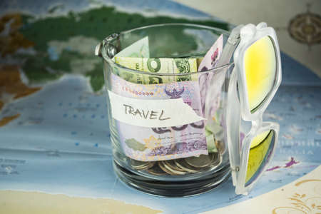 holiday budget: Travel budget money savings in a glass jar on world map