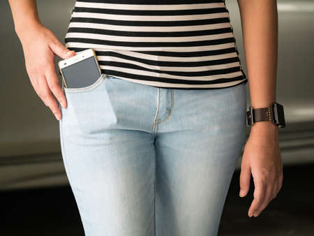 pocket: Smart phone in pocket of girls jeans Stock Photo