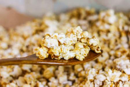Popcorn on a wooden ladle Фото со стока