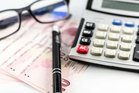 Turkish Money Banknotes on the white surface with pen, glasses and calculator. G