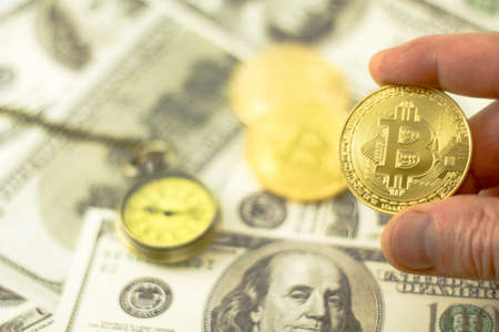 Golden Bitcoin coin on blurred us dollar bills background, copy space