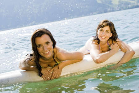 girls relaxing on a surfboard in austrian lake. photo
