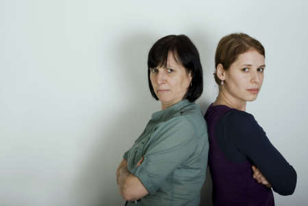 Mother and daughter offended after conflict standing in front of turquoise wall. Stock Photo - 7449538