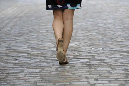 Shot of woman legs walking on cobbled pavement. Stock Photo