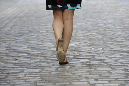 Shot of woman legs walking on cobbled pavement. Stock Photo