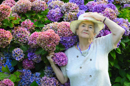 Old senior woman with hat showing her flowers.