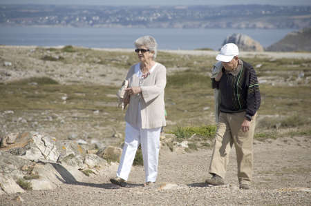 Senior couple walking along the coast of Brittany Stock Photo - 7730184