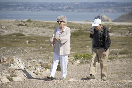 Senior couple walking along the coast of Brittany Stock Photo - 7730184