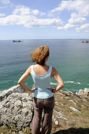 Young woman watching the coastline of the atlantic ocean in Brittany, France photo