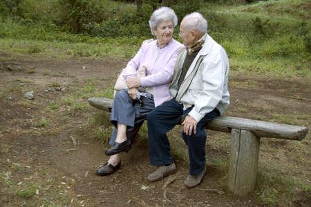 Old happy senior couple sitting on bench photo