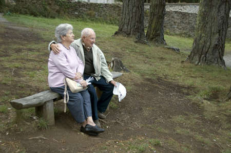 Old happy senior couple sitting on bench photo