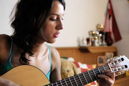 Young beautiful woman playing guitar in her room. Stock Photo - 7816864