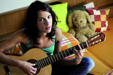 Young beautiful woman playing guitar in her room. photo