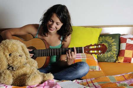 Beautiful teen girl playing guitar in her bedroom photo