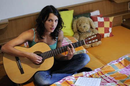 Beautiful teen girl playing guitar in her bedroom Stock Photo - 7981221