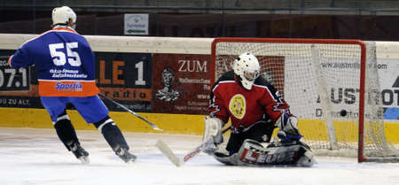 oldies: ZELL AM SEE, AUSTRIA - SEPTEMBER 30: Austrian Icehockey Classic Tournament. Tommi Aaltonen scores against Zell am See Goalie Peter Hochwimmer. Game Zell am See Oldies vs. Pallojussit (Result 3-3) on September 30, 2010 in Zell am See