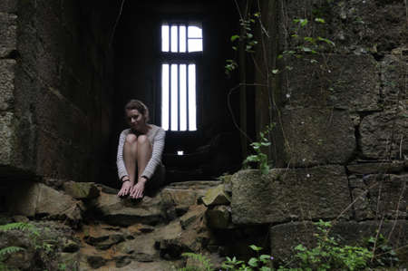 Young woman sitting in dungeon of old castle in Brittany photo