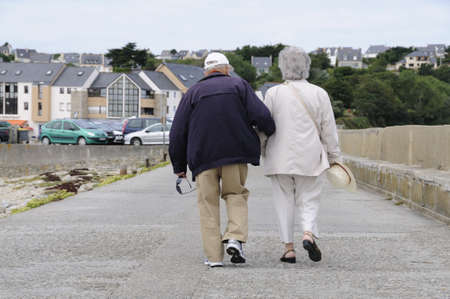 Happy senior couple walking along the coast of brittany photo