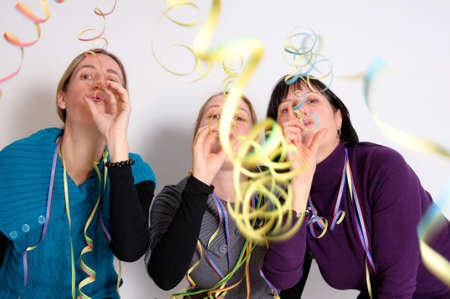 Two young women and one senior woman celebrating New year's eve. Shot taken in front of white background Stock Photo