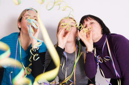 gente loca: Dos j�venes y una mujer senior, celebrando el fin de a�o de. Filmado en frente de fondo blanco