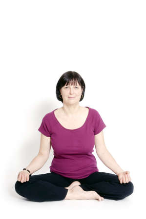 Aged woman sitting in lotus seat practicing yoga. photo