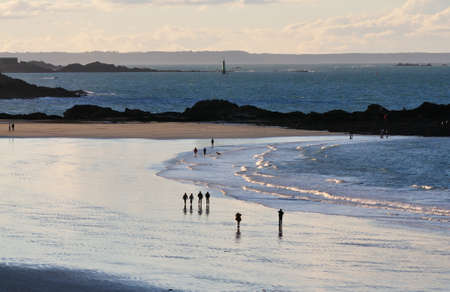 People walking at the beach of Saint-Malo at sunset. Stock Photo