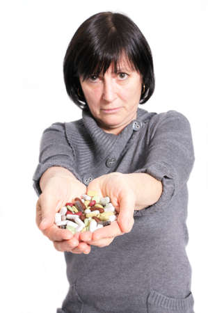 Aged woman holding a pile of pills and capsules in her hands photo