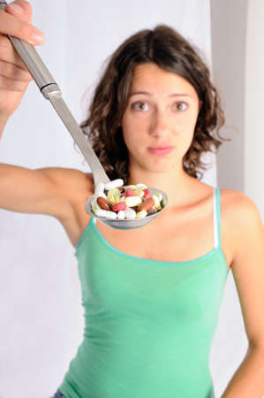 adverse reaction: Shot of cute girl with spoon full of pills. Concept shot for alternative medicine Stock Photo