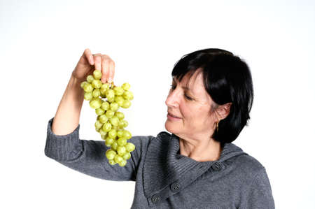 Aged woman with bunch of fresh grapes isolated on white background photo