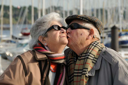 Old senior man kissing his wife at the yacht harbor. photo