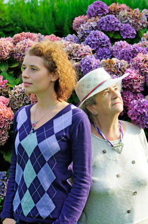 Old senior woman and young woman looking different ways photo