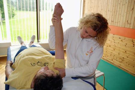 physical pressure: SAALFELDEN, AUSTRIA - AUGUST 30: physical therapist exercising with senior rheumatism patient on August 30, 2007 at rehabilitation center in Saalfelden, Austria. Editorial
