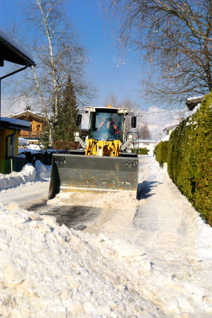 Snowplow cleaning streets in austria after heavy snow storm. photo