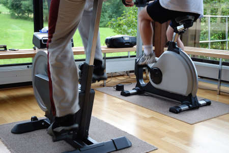 home gym: Closeup on legs of people cycling in fitness center