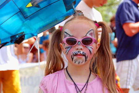 MITTERSILL, AUSTRIA - JUL 4: Children face painting at the supporting programme of the Watersports Event  called Erdinger Sautrogrennen on July 4, 2010 at the Zierteich in Mittersill, Austria