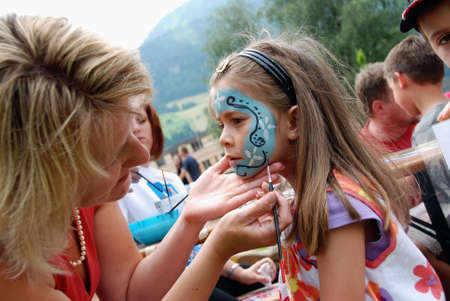 kids painting: MITTERSILL, AUSTRIA - JUL 4: Children face painting at the supporting programme of the Watersports Event Erdinger Sautrogrennen on July 4, 2010 at the Zierteich in Mittersill, Austria Editorial