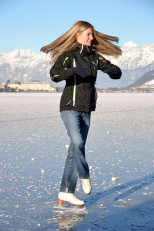 Pirouette of young woman figure skating at frozen lake of zell am see in austria Stock Photo