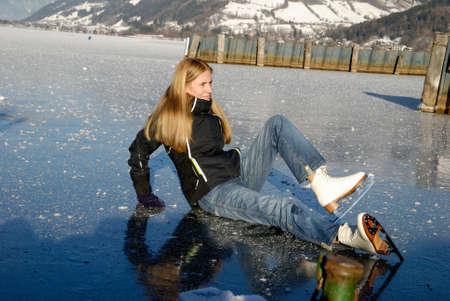 to skate: Ca�da de la mujer para el hielo mientras patinar sobre el lago congelado