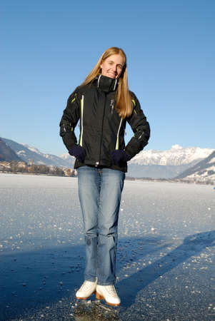 Young woman ice skating on frozen lake on a sunny day photo