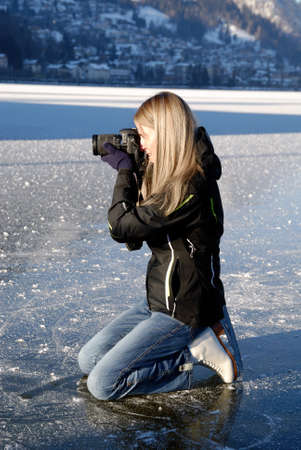 Woman kneeing on ice taking pictures on frozen lake photo