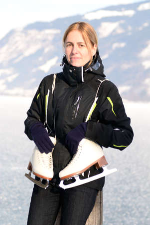 Pretty woman with ice skating schoes at frozen lake photo