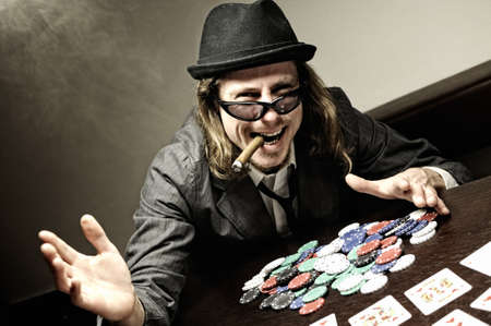 gamblers: Man with hat and glasses playing underground poker. Stock Photo