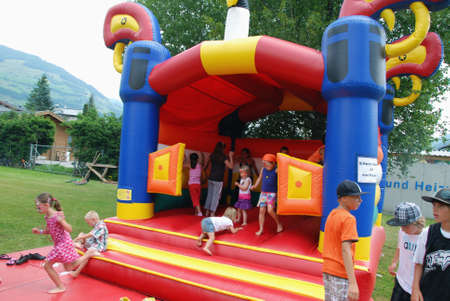 MITTERSILL, AUSTRIA - JUL 4: Children playing in inflatable castle at the supporting programme of the Water fun Event Erdinger Sautrogrennen on July 4, 2010 at the Zierteich in Mittersill, Austria