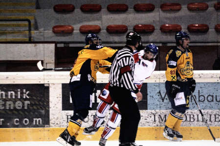 bodycheck: ZELL AM SEE, AUSTRIA - FEB 1: Austrian National League. Referee watching hard hit. Game EK Zell am See vs. ATSE Graz (Result 4-1) on February 1, 2011, at hockey rink of Zell am See Editorial