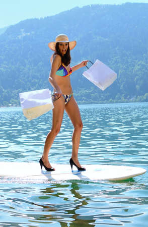 Concept of woman shopping walking on surfboard with shopping bags. Stock Photo